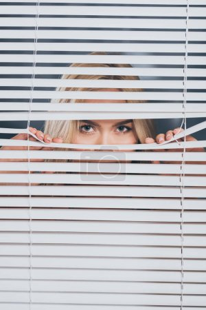 young woman looking at camera and peeking through blinds, mistrust concept