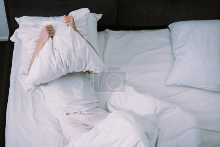 Photo for Depressed woman covering face with pillow while lying in bed at home - Royalty Free Image