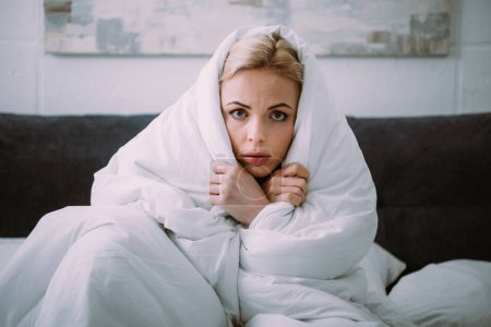 Frightened woman covered in blanket looking at cam...