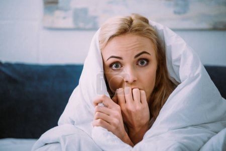 Photo for Scared woman covered in blanket biting hand and looking at camera in bed - Royalty Free Image