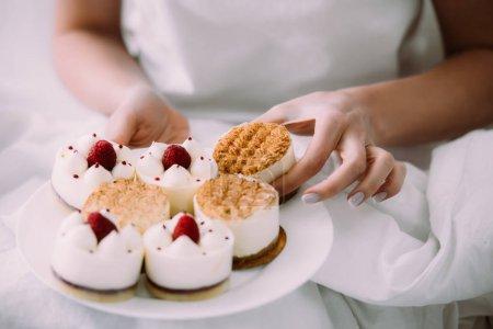 Photo pour Vue recadrée de la femme tenant un des gâteaux sur l'assiette dans le lit - image libre de droit