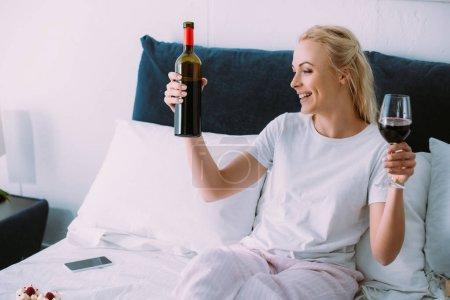 belle femme souriante en pyjama tenant bouteille de vin et verre au lit à la maison