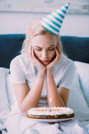 mujer deprimida mirando pastel mientras celebra cumpleaños en la cama solo