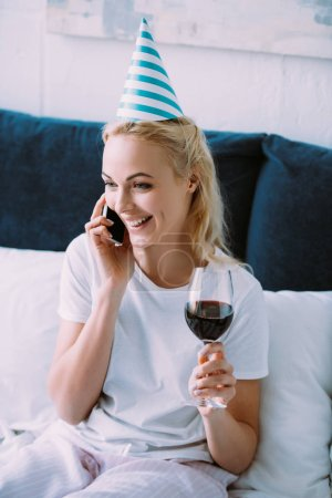 Photo for Smiling woman in party hat celebrating birthday, holding glass of wine and talking on smartphone in bed at home - Royalty Free Image