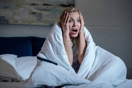 Photo for Scared woman covered in blanket with hands on head screaming while watching tv in bed at home - Royalty Free Image