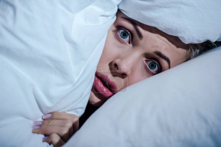 Scared woman hiding behind blanket and looking at ...
