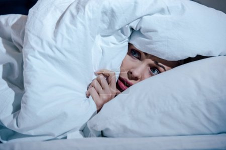 Scared woman hiding behind blanket in bedroom at h...