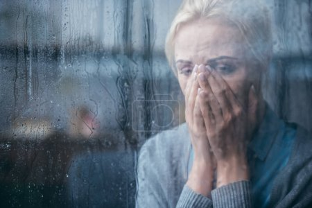 Photo for Sad adult woman crying and covering face with hands at home through window with raindrops - Royalty Free Image