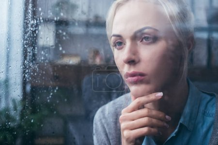 Photo for Sad thoughtful adult woman touching face at home through window with raindrops - Royalty Free Image