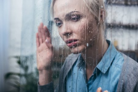 Photo for Depressed adult woman touching window with raindrops - Royalty Free Image