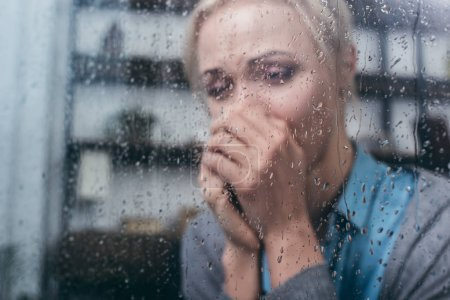 Photo for Depressed adult woman with folded hands at home through window with raindrops - Royalty Free Image