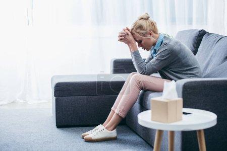Foto de Mujer deprimida con las manos dobladas sentada en casa en el sofá - Imagen libre de derechos