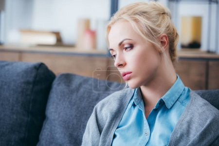 Photo for Selective focus of beautiful upset woman sitting on couch at home - Royalty Free Image