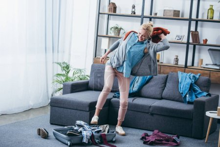 irritated woman throwing clothes in