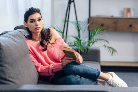 Photo for Attractive indian student sitting on sofa with book - Royalty Free Image