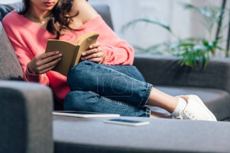 Photo for Cropped view of female student sitting on sofa and reading book - Royalty Free Image