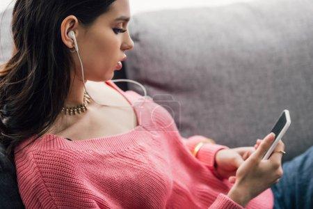 Photo pour Attrayant femme indienne écouter de la musique avec des écouteurs et en utilisant un smartphone - image libre de droit
