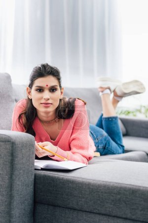 Photo for Female indian student with bindi studying with notebook on sofa - Royalty Free Image