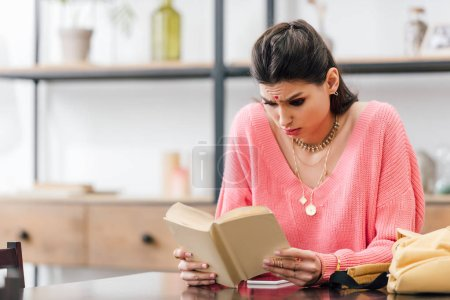 Photo for Indian woman with bindi studying at home and reading book - Royalty Free Image