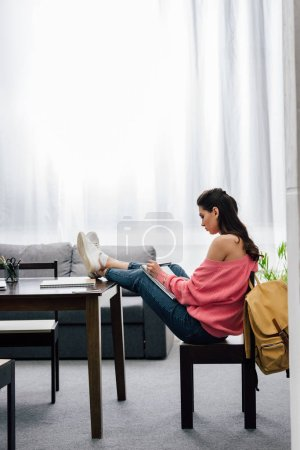Photo for Female indian student writing in notebook and studying at home - Royalty Free Image