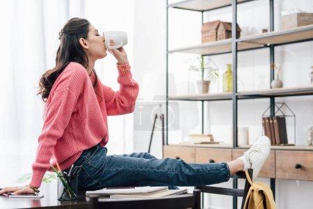 Photo pour Étudiant indien boire du café à la maison avec des cahiers - image libre de droit