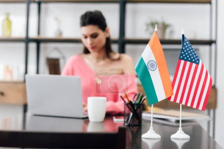Photo for Selective focus of american and indian flags on table and girl studying with laptop - Royalty Free Image