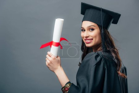 Photo for Smiling female indian student in academic gown and graduation cap holding diploma, isolated on grey - Royalty Free Image