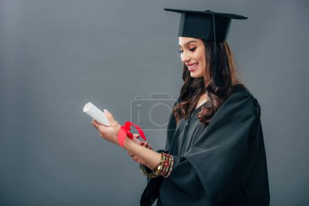 Photo for Happy indian student in academic gown and graduation hat holding diploma, isolated on grey - Royalty Free Image