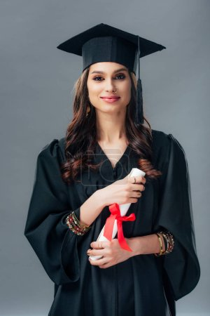 Photo for Happy female indian student in academic gown and graduation hat holding diploma, isolated on grey - Royalty Free Image