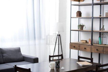 Photo pour Vide salle de séjour avec table, canapé, lampes et étagères - image libre de droit