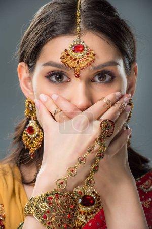 Photo pour Fille indienne choquée, fermer la bouche avec les mains, isolé sur fond gris - image libre de droit