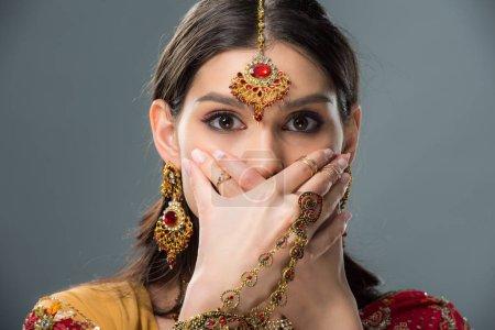 Photo pour Élégante jeune indienne choquée fermant la bouche avec les mains, isolé sur fond gris - image libre de droit