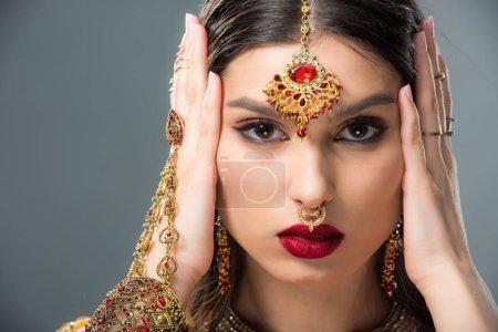 Photo pour Belle femme indienne avec bindi touchant la tête, isolé sur fond gris - image libre de droit