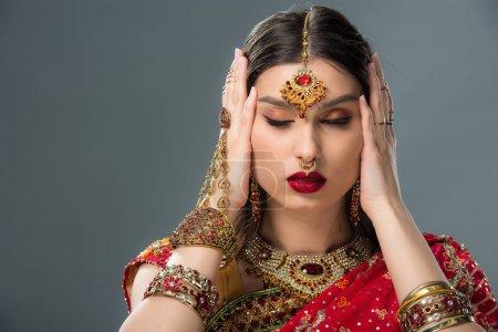 Photo pour Attrayant indien femme avec bindi toucher la tête, isolé sur gris - image libre de droit
