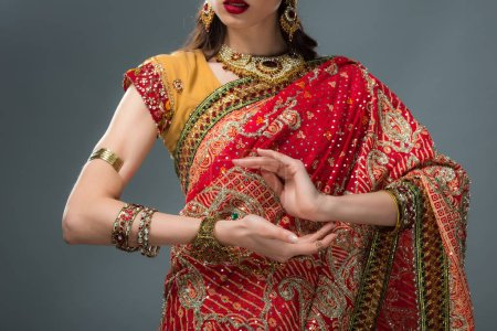 Photo for Cropped view of attractive indian woman gesturing in traditional clothing, isolated on grey - Royalty Free Image