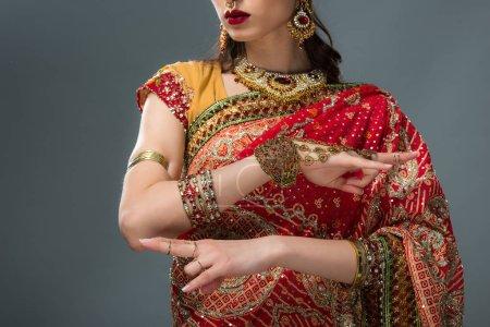 Photo pour Vue recadrée de femme indienne en vêtements traditionnels, montrant la fenêtre sagesse Mudra, isolé sur fond gris - image libre de droit