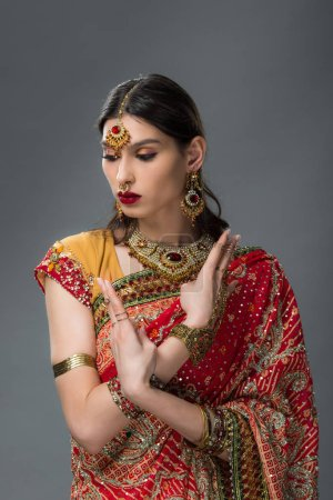 Photo for Attractive indian woman posing in traditional clothing showing mudra, isolated on grey - Royalty Free Image