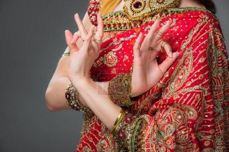 Photo pour Vue recadrée de femme indienne en montrant des vêtements traditionnels gyan mudra, isolé sur fond gris - image libre de droit