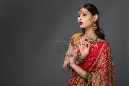 Photo pour Jolie femme indienne en montrant des vêtements traditionnels gyan mudra, isolé sur fond gris - image libre de droit