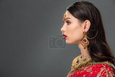 Photo pour Vue latérale d'une jolie femme indienne posant en sari et bindi traditionnels, isolée sur gris - image libre de droit