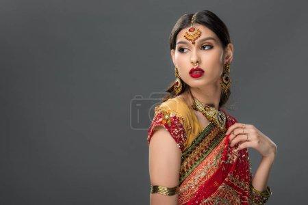 Photo pour Femme indienne posant en sari et accessoires traditionnels, isolée sur gris - image libre de droit