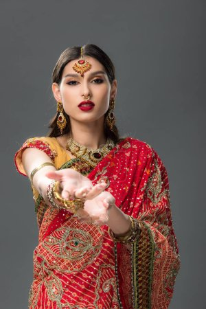 Photo for Elegant woman gesturing in traditional indian sari and accessories, isolated on grey - Royalty Free Image
