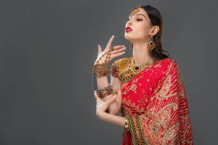 Photo pour Séduisante femme indienne gestuelle en sari et accessoires traditionnels, isolée sur gris - image libre de droit