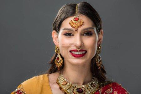 Photo pour Heureuse femme indienne posant dans sari traditionnel et accessoires, isolé sur gris - image libre de droit