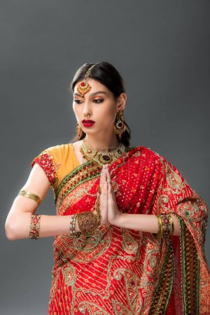 Photo pour Belle femme indienne dans les vêtements traditionnels avec namaste mudra, isolé sur gris - image libre de droit