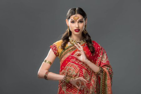 Photo for Attractive indian woman in sari and accessories with gyan mudra, isolated on grey - Royalty Free Image