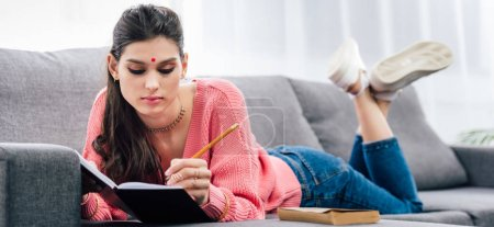 Photo for Indian student with bindi writing in notebook on sofa with book - Royalty Free Image
