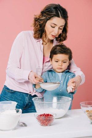 Photo pour Belle mère avec adorable petit fils, tamiser la farine avec tamis ensemble isolée sur Rose - image libre de droit
