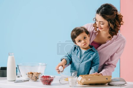 Photo for Mommy helping adorable little son holding egg and looking at camera on bicolor background - Royalty Free Image