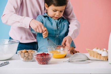 Foto de Lindo niño batir huevos con balón mientras madre ayudándole sobre fondo bicolor - Imagen libre de derechos